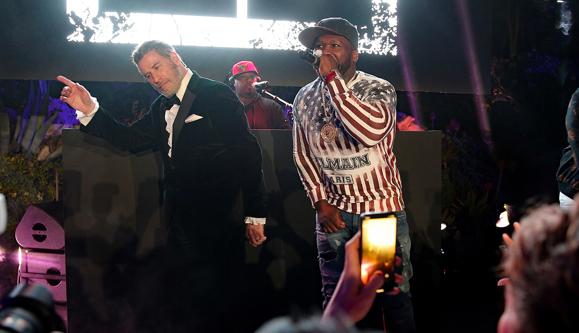 John Travolta on stage as  Singer 50 Cent performs.