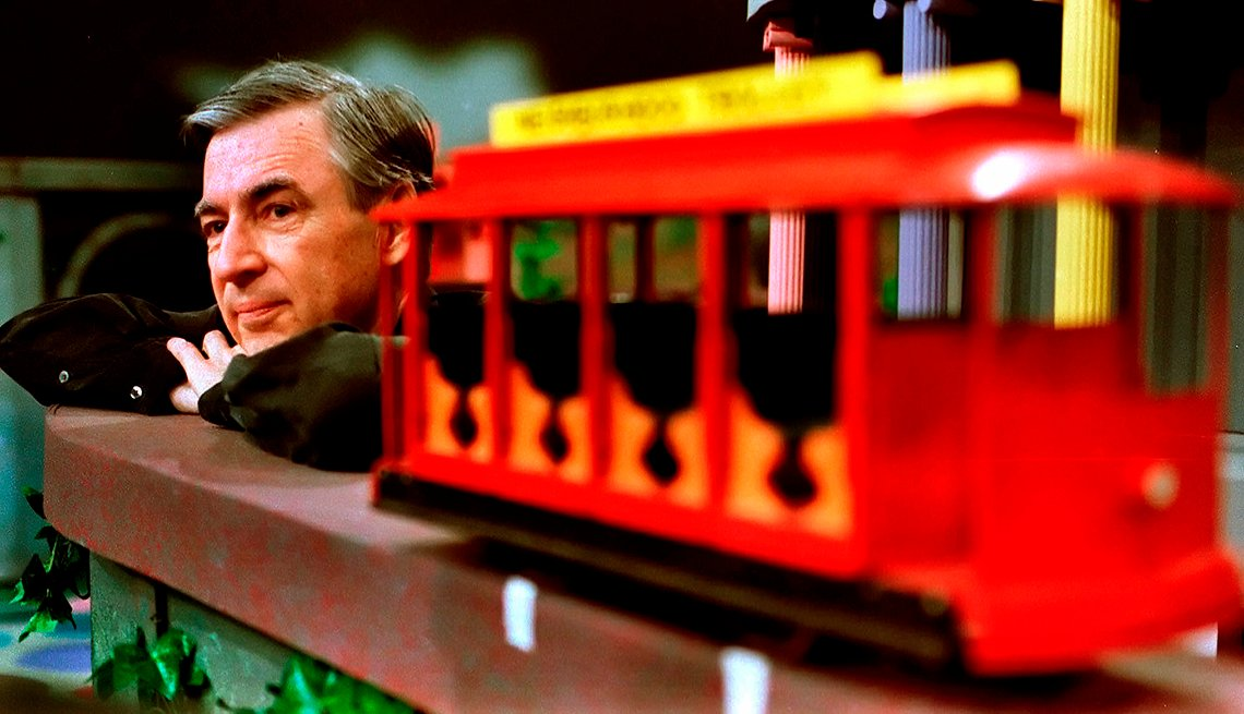 Mister Rogers sitting behind the famous trolley on  the set of