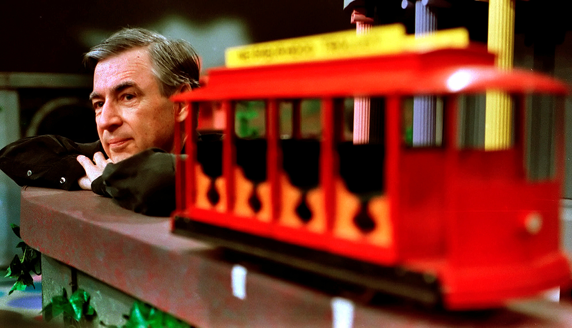 """Mister Rogers sitting behind the famous trolley on  the set of """"Mister Rogers Neighborhood."""""""