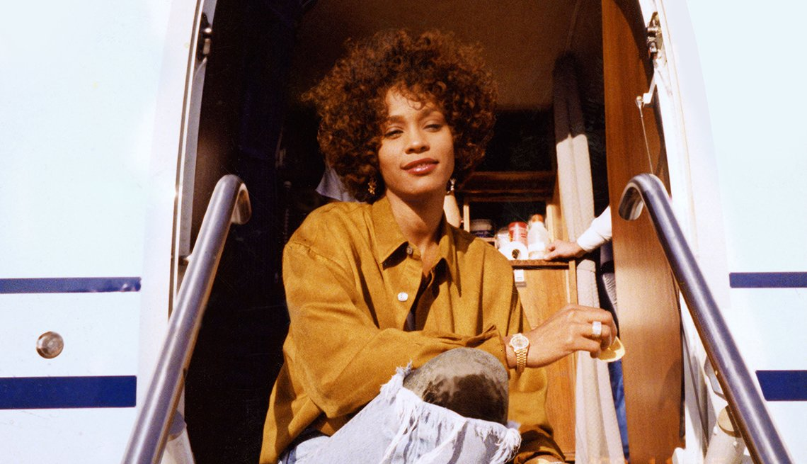 Whitney Houston sits on stairs of plane in a scene from the documentary 'Whitney'