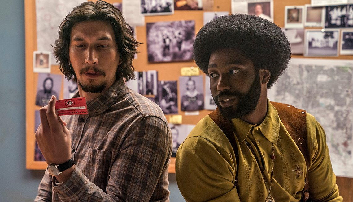 Adam Driver and John David Washington sitting next to each other.