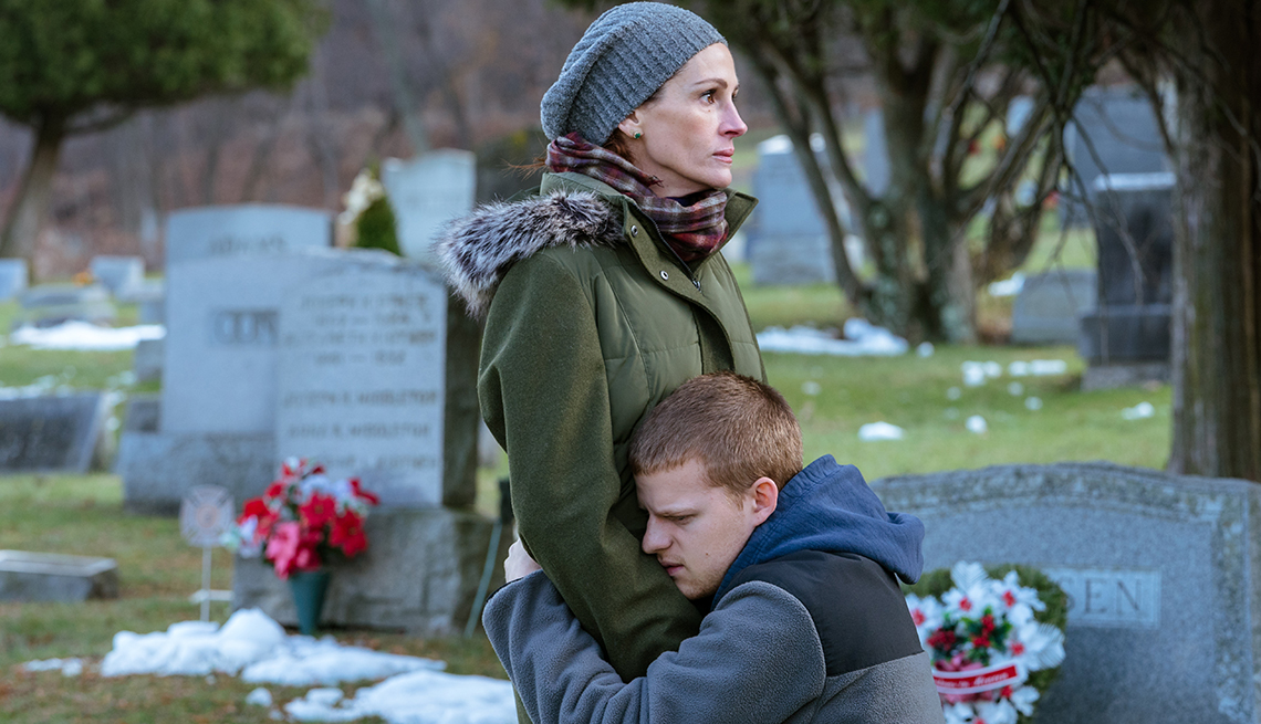 item 11 of Gallery image - Lucas Hedges bent down hugging Julia Roberts at a cemetery.