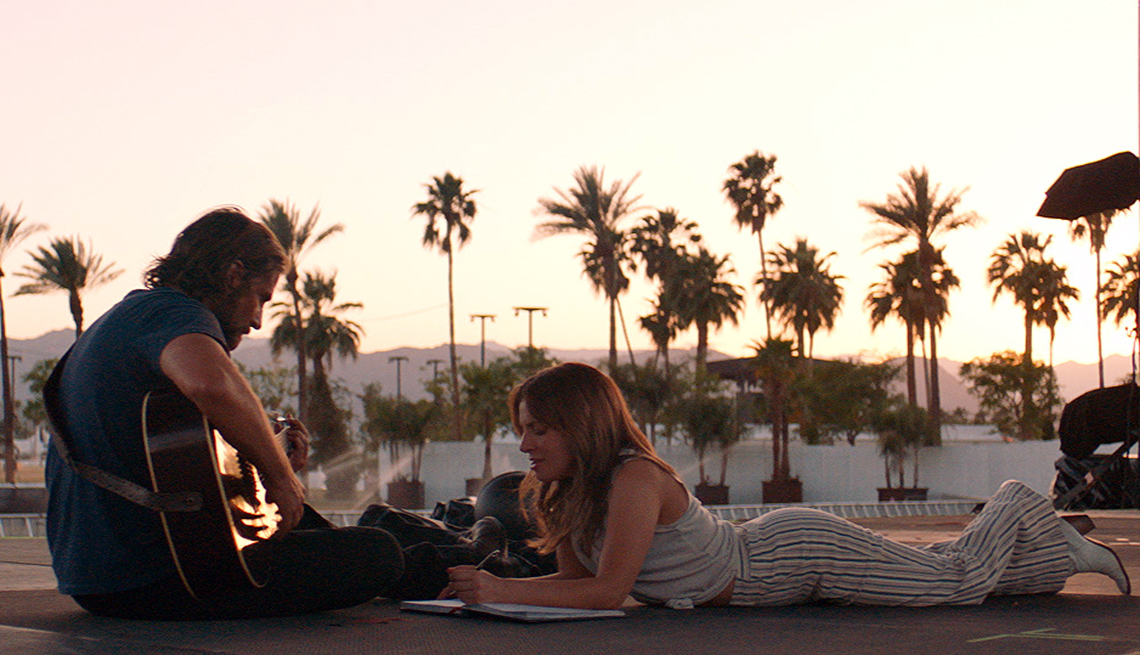 item 3 of Gallery image - Bradley Cooper and Lady Gaga sitting on the ground with palm trees in the distance.