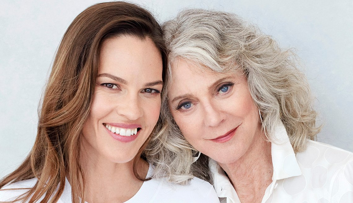 Hilary Swank and Blythe Danner smiling with their heads touching.