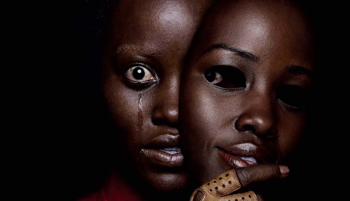 Lupita Nyong'o cries in terror as she removes a mask of her face in a creepy poster for US