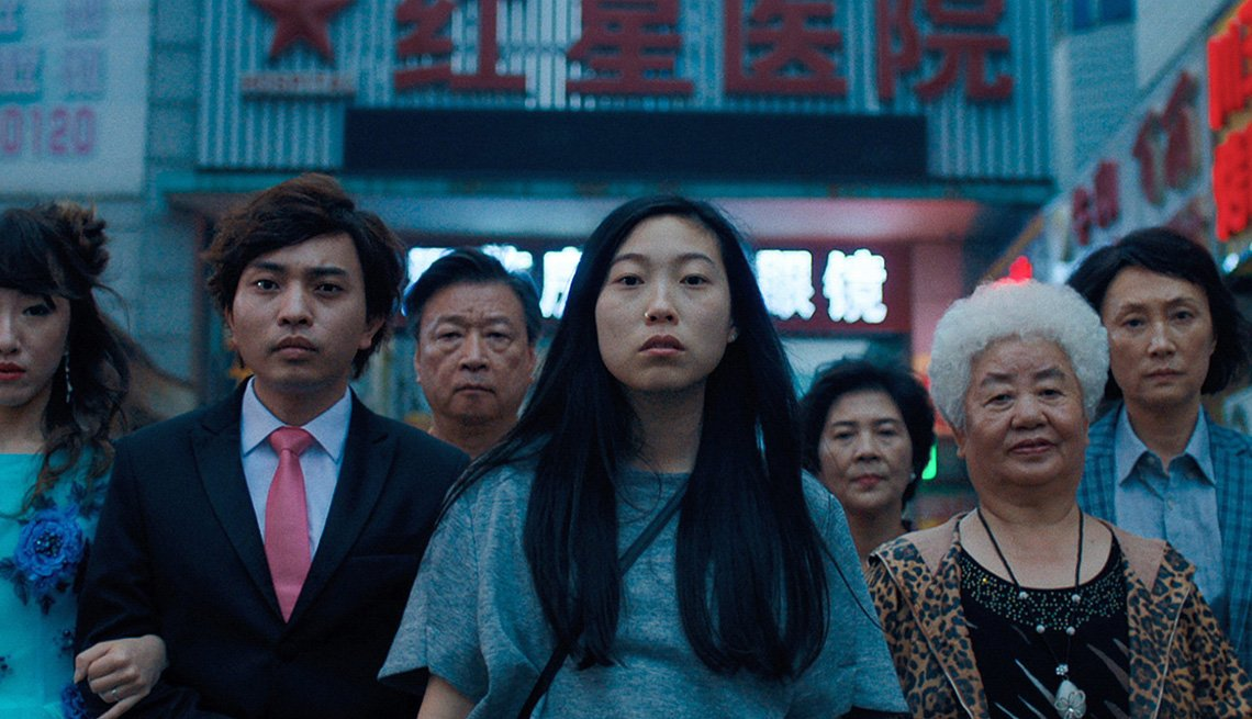 Awkwafina and cast members that play her family stand on the street in a scene from the movie The Farewell