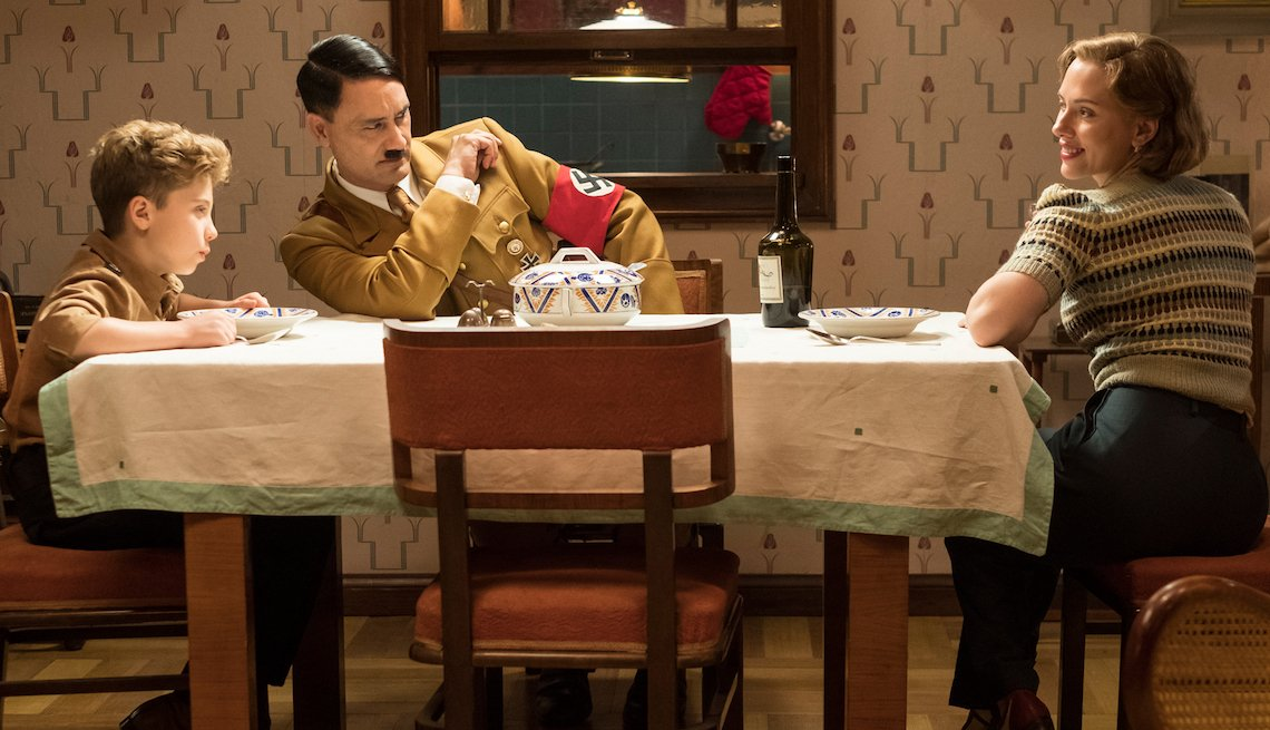 (From L-R): Jojo (Roman Griffin Davis) has dinner with his imaginary friend Adolf (Writer/Director Taika Waititi), and his mother, Rosie (Scarlet Johansson).