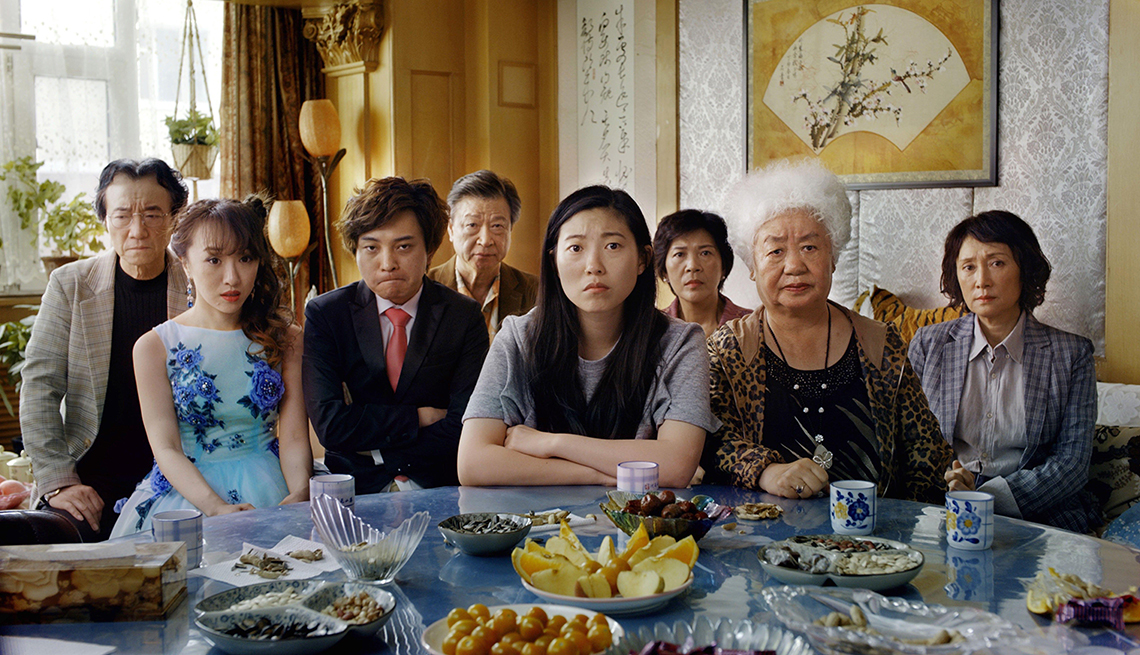 item 9 of Gallery image - The cast of The Farewell seated in front of a table filled with food