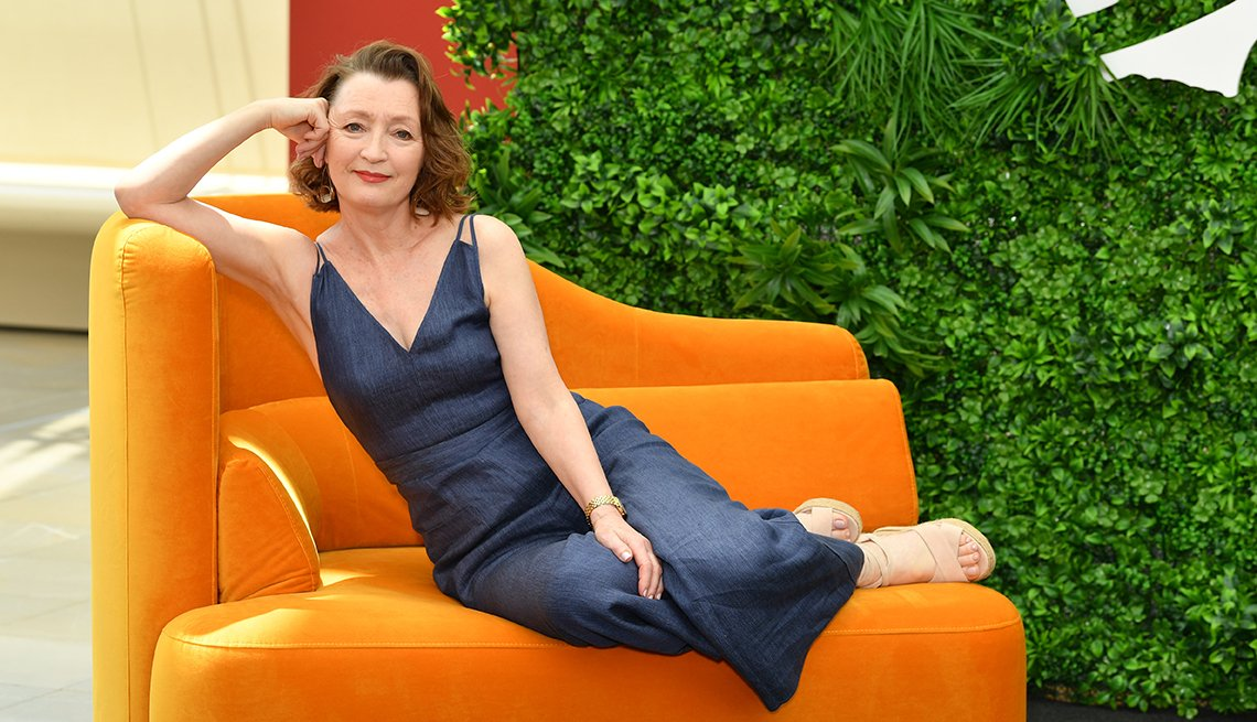 actress leslie manville reclines on an orange chair