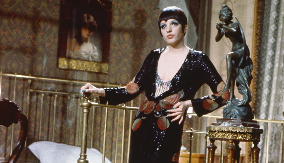 Liza Minnelli wearing a low cut long black dress posing beside a bed for the film Cabaret