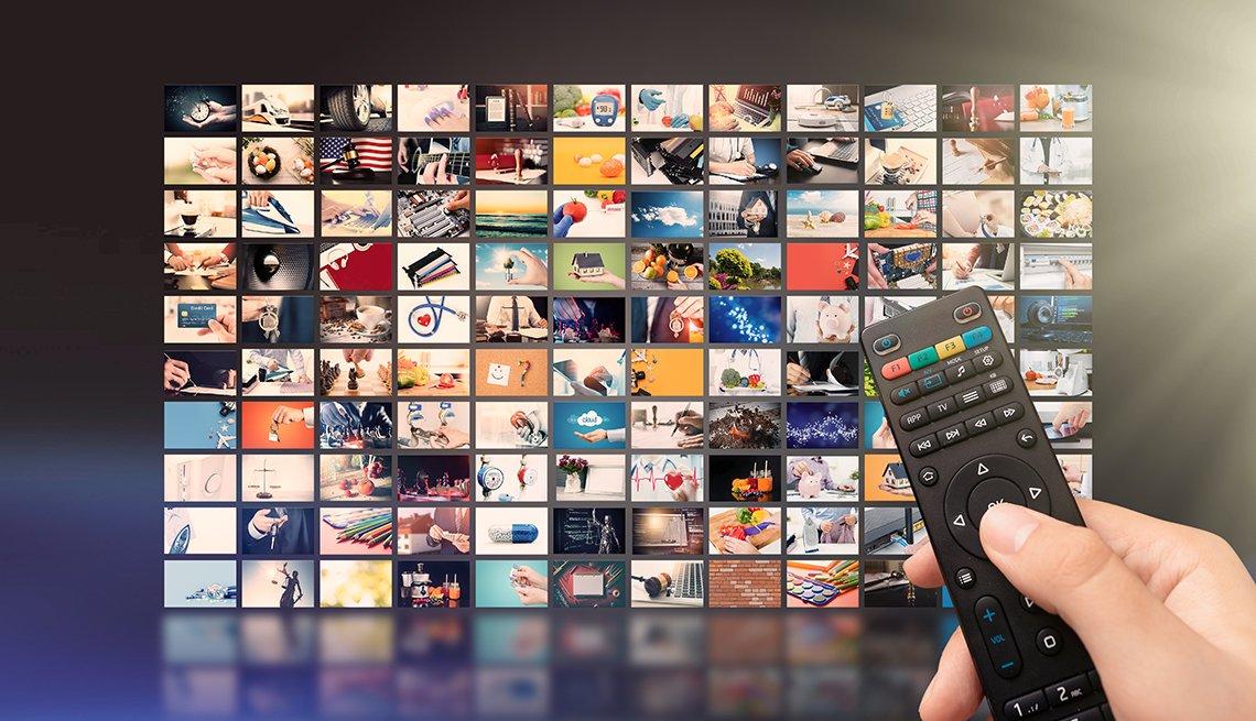 Persona sosteniendo un control remoto que apunta a una pantalla con diferentes aplicaciones de tv.
