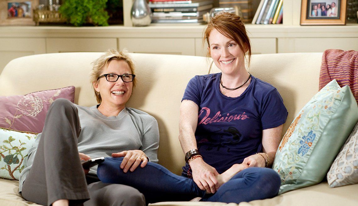 Annette Bening and Julianne Moore sitting on a couch in the film The Kids Are All Right