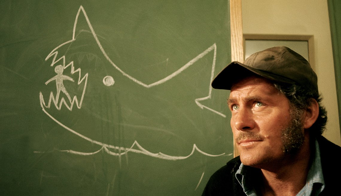 Actor Robert Shaw in front of a chalkboard showing a drawing of a shark eating a person