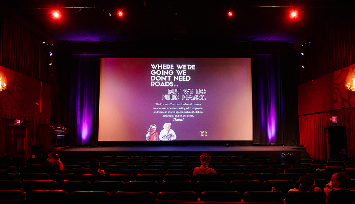 A public service health announcement is displayed on the screen at a nearly empty movie theater in New Orleans