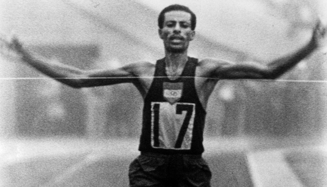Abebe Bikila cruza la línea de meta para ganar la medalla de oro en el maratón masculino e imponer un récord en los Juegos Olímpicos de verano de 1964.