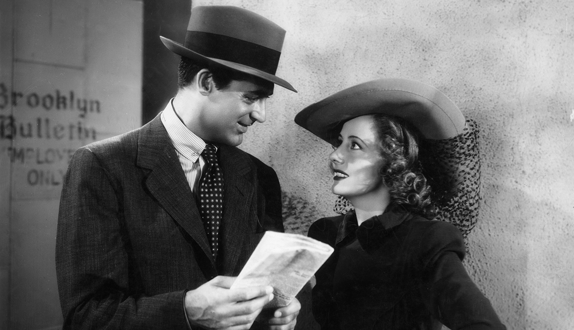 """Cary Grant holds a folded newspaper and looks at Irene Dunne while they stand outside the employee's entrance of the Brooklyn Bulletin in the film """"Penny Serenade."""""""