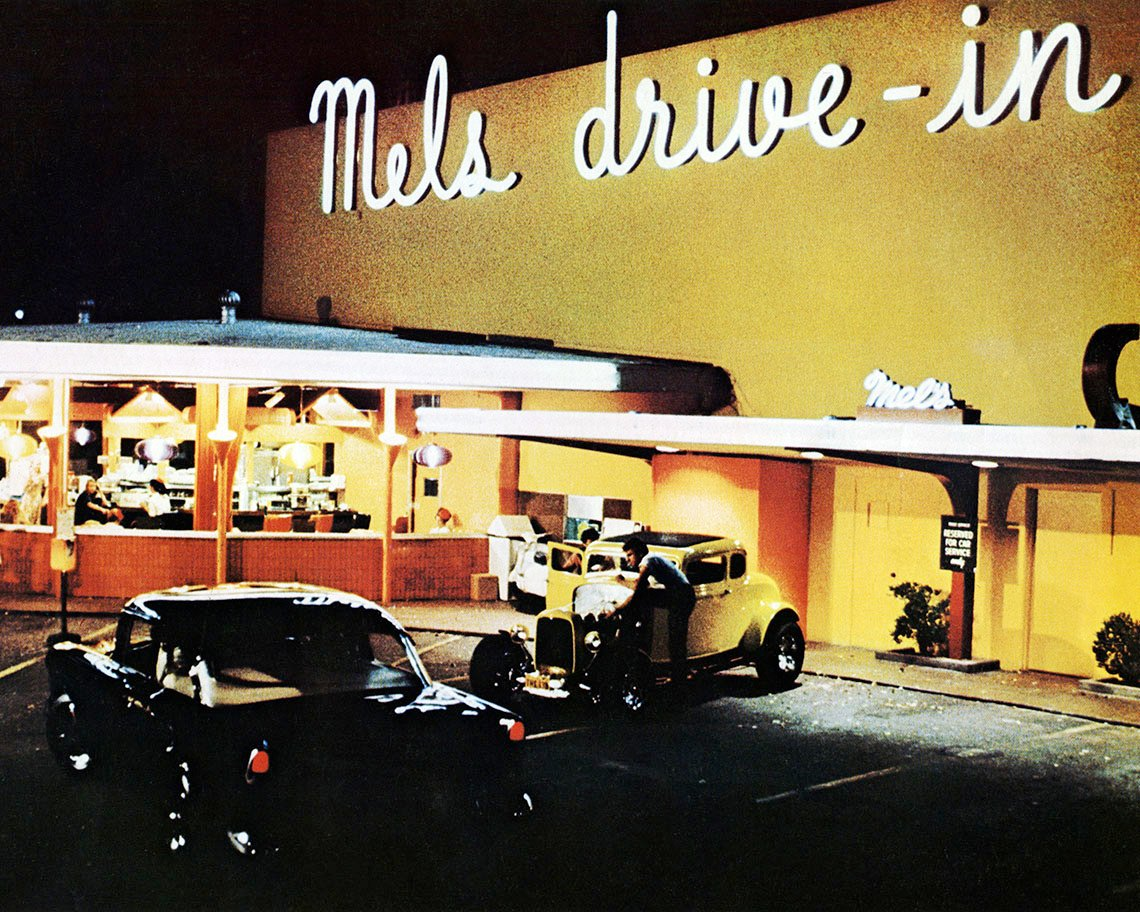 A night time scene outside of Mels Drive In from the film American Graffiti