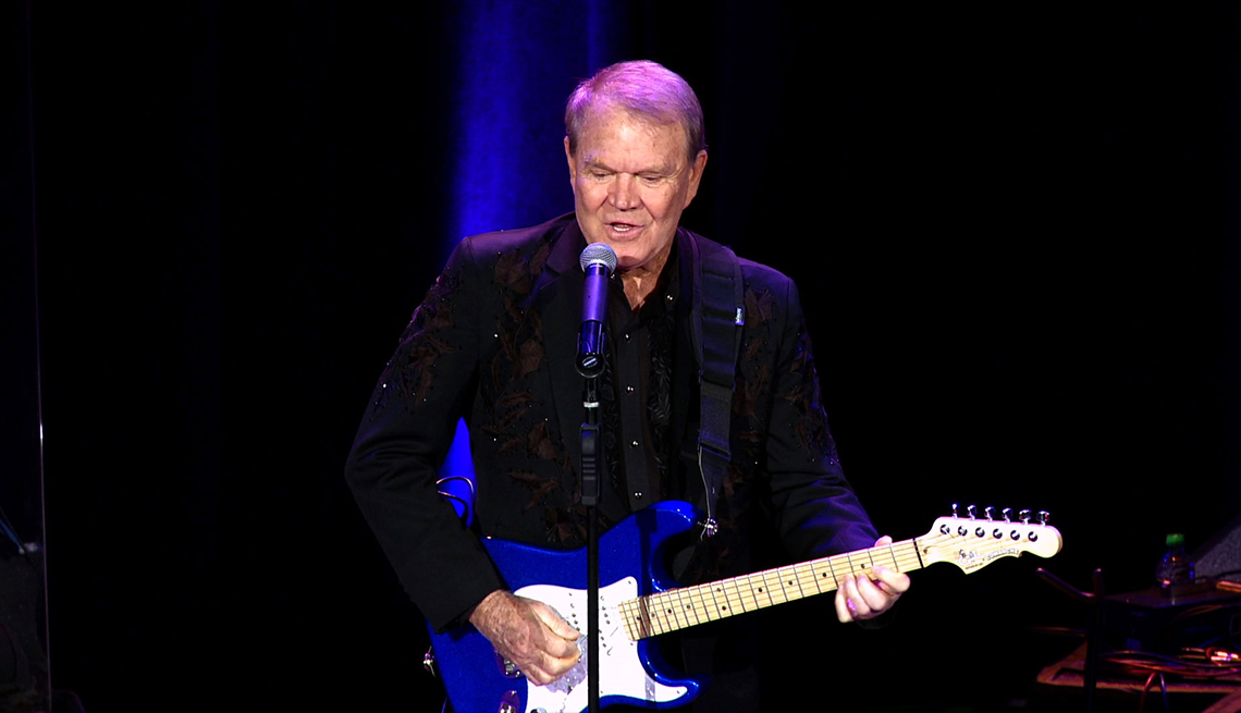 Glen Campbell performing on stage with his guitar in the documentary Glen Campbell: I'll Be Me