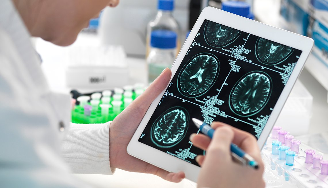 A scientist viewing a patient's brain scan on digital tablet in laboratory