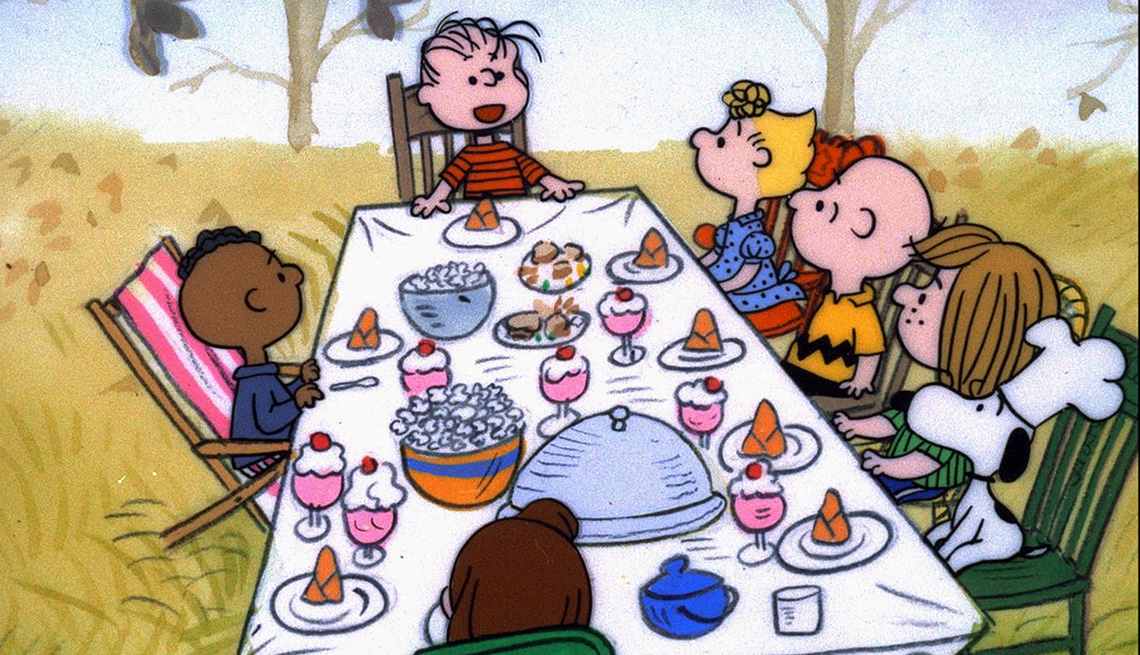 Charlie Brown and his friends sit around the dinner table in a scene from A Charlie Brown Thanksgiving