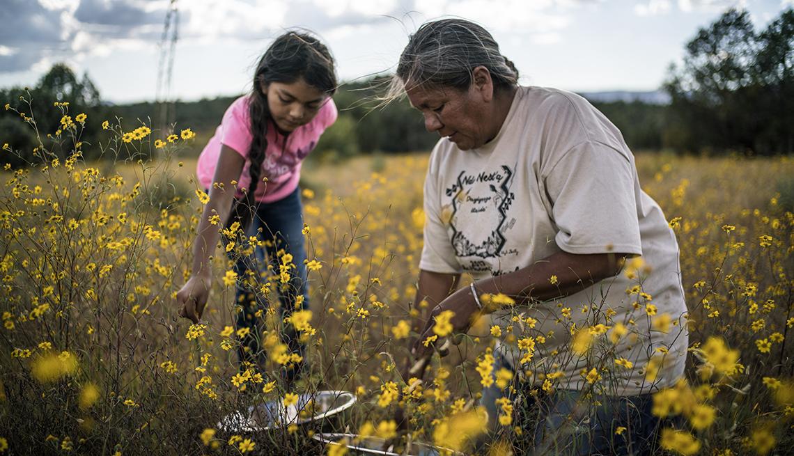 Una niña y una mujer recogen flores y plantas en una escena del documental Gather.