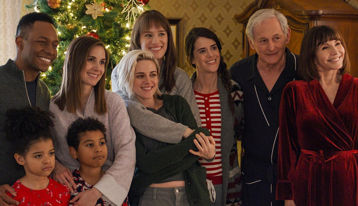 Burl Moseley, Alison Brie, Kristen Stewart, Mackenzie Davis, Mary Holland, Victor Garber and Mary Steenburgen together in front of a Christmas Tree in the film Happiest Season