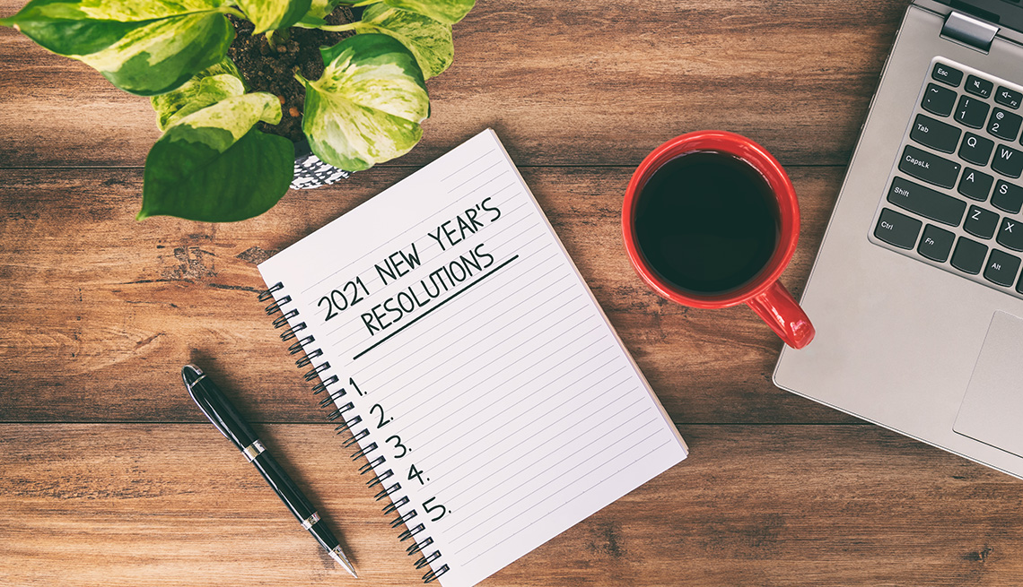A notepad with 2021 New Year's Resolutions written on a page with a laptop and a cup of coffee nearby on top of a wooden desk