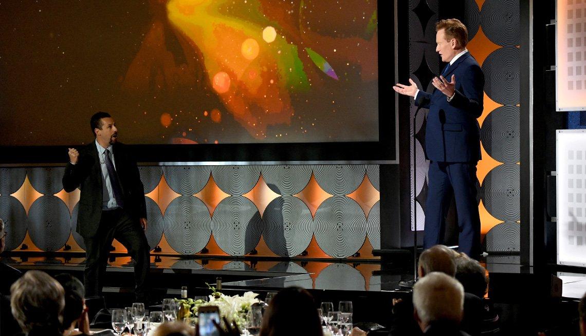 Conan O Brien abre sus manos cuando Adam Sandler llega al escenario de Movies for Grownups Awards.