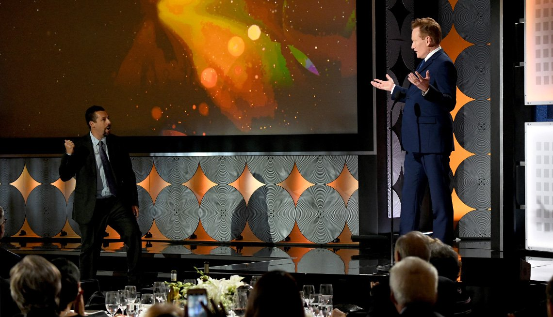 Conan O Brien raises his hands as Adam Sandler comes to the stage too early during the presentation of the Best actor award at the Movies for Grownups Awards