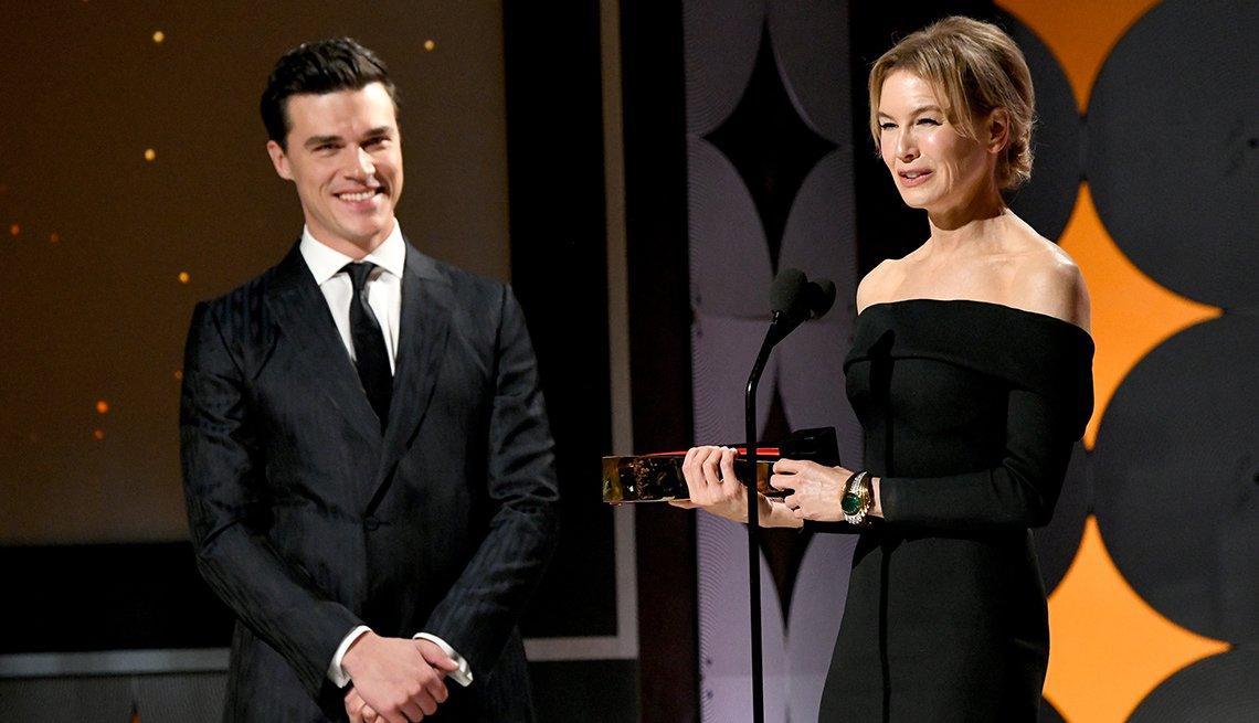 Finn Wittrock mira a Renee Zellweger mientras da su discurso después de recibir su premio como mejor actriz en los premios Movies for Grownups.