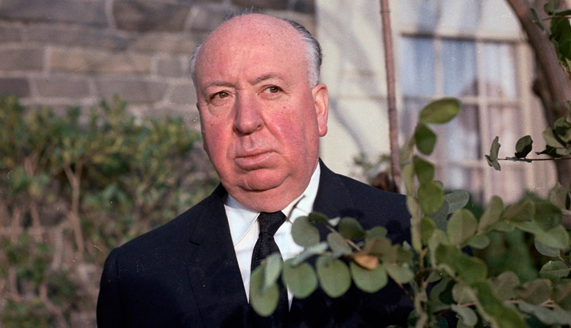 Director Alfred Hitchcock standing by a bush
