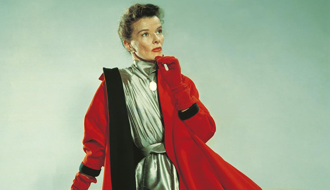 La actriz Katharine Hepburn posa con un vestido plateado y un abrigo rojo.