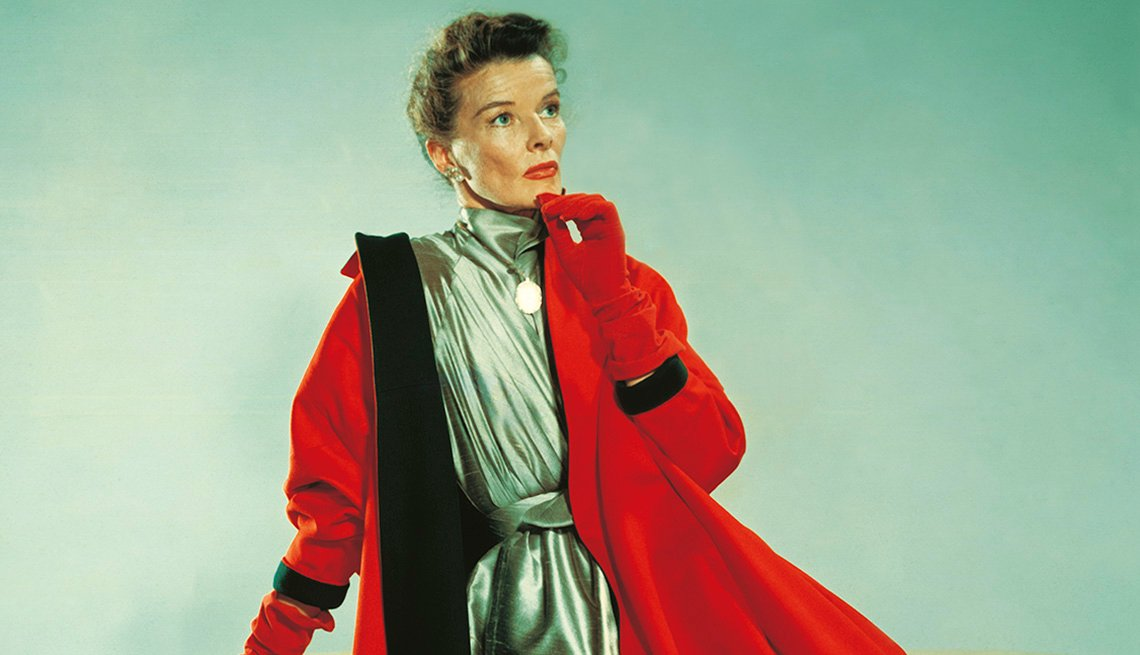 Katharine Hepburn poses in a silver dress and a red coat