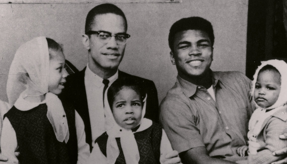 Malcolm X and Muhammad Ali sitting next to each other while holding their daughters in their laps