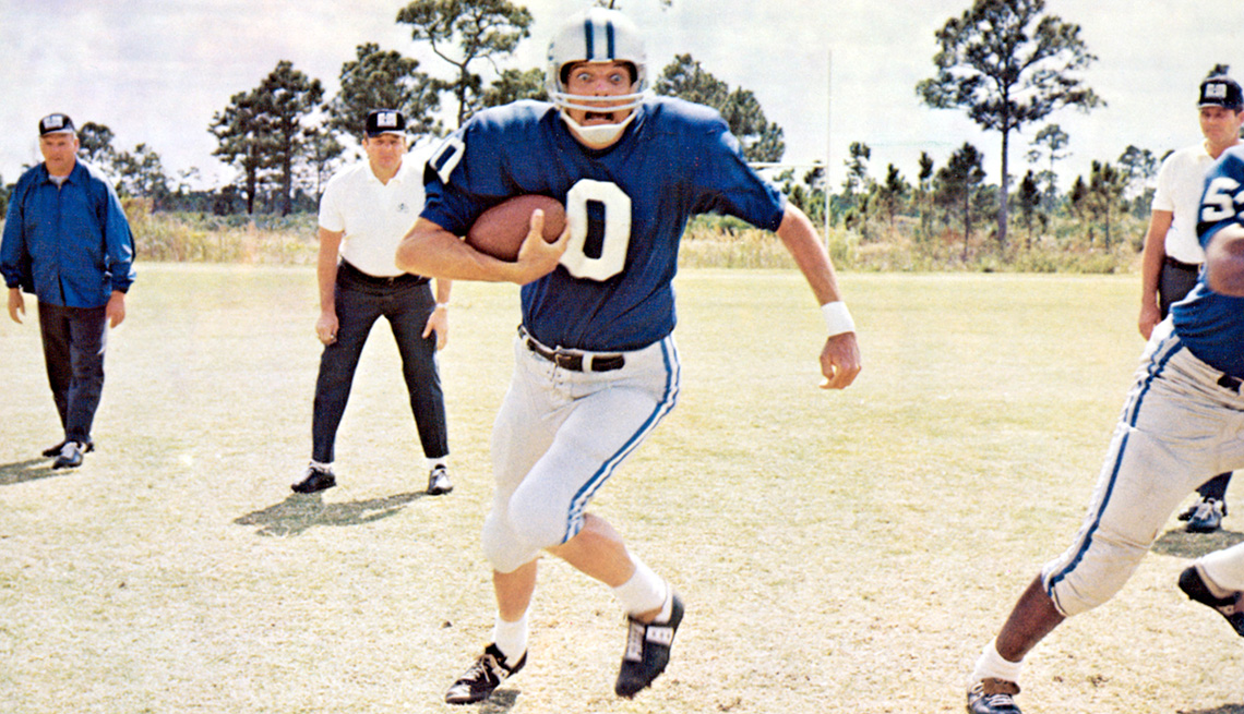 Alan Alda carrying a football with a worried look on his face in a scene from the film Paper Lion