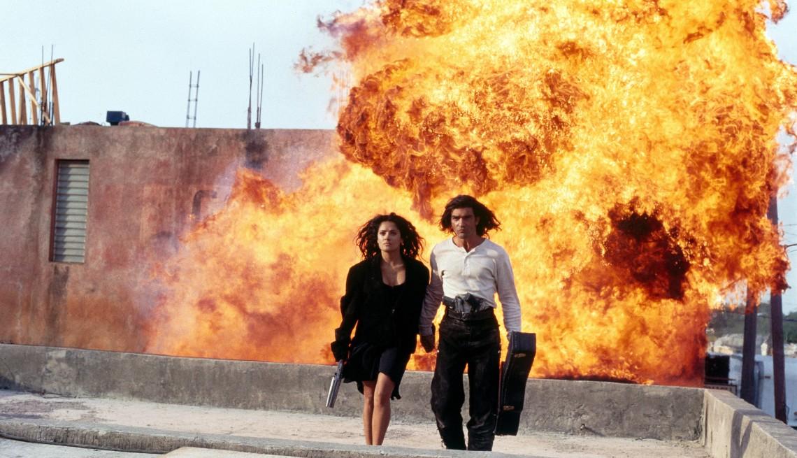 item 3 of Gallery image - Salma Hayek and Antonio Banderas walk away from a fiery explosion in the film Desperado