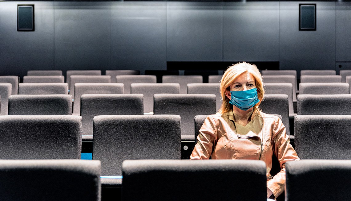 A woman wearing a protective face mask sitting in an empty movie theater