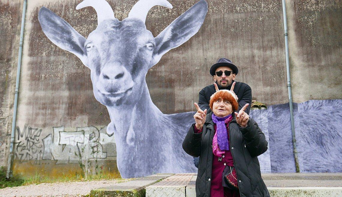 La cineasta Agnès Varda y el fotógrafo y muralista JR con sus dedos levantados en un recorrido por Francia en su documental, 'Faces Places'.