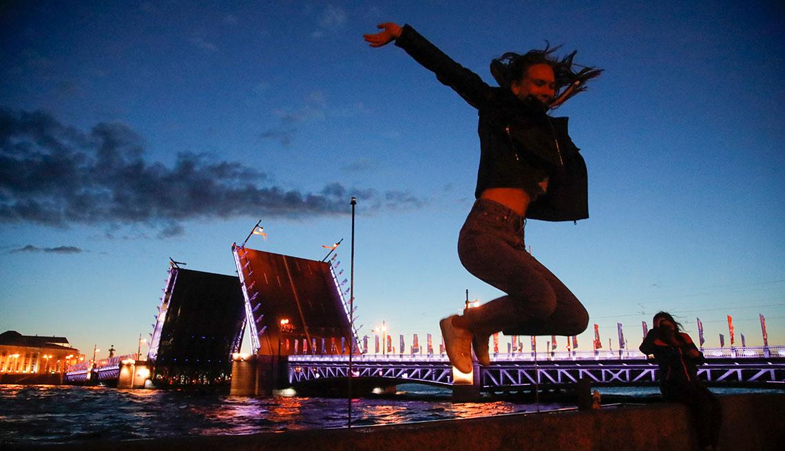 Una mujer salta cerca del puente Dvortsovy en San Petersburgo, Rusia