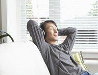 Hombre escuchando música en casa con auriculares - AARP Radio por internet