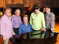 The band Beach Boys standing around a piano