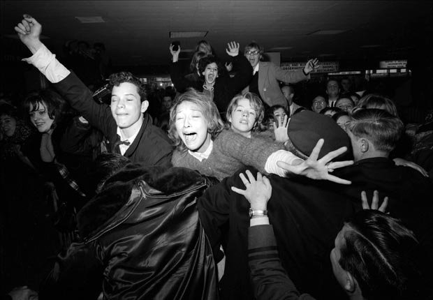 rock n roll enthusiasts rocked the conservative culture in America during the 1960s- beatles fans scream at kennedy airport