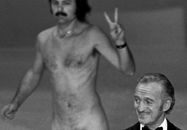 David Niven presents at the 1974 Academy Awards show ]as a streaker named Robert Opel crosses the stage behind him.
