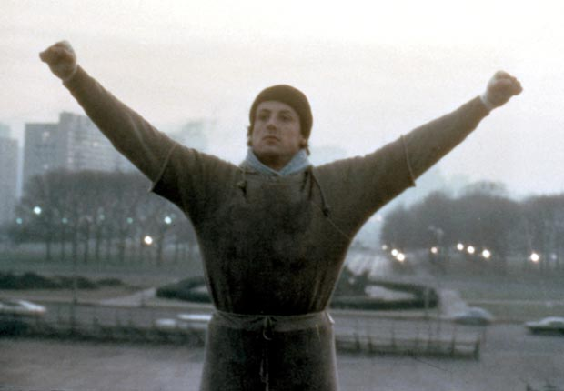 Sylvester Stallone in 'Rocky' when the titular character raises his arms in victory as he trains for a boxing match that he subsequently loses.