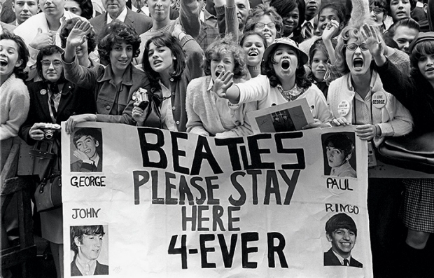 Screaming girls in a crowd holding a large banner reading 'Beatles Please Stay Here 4-Ever', Beatlemania - 50 years later