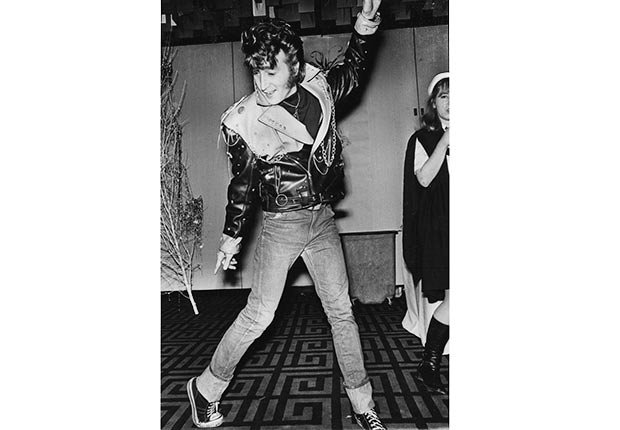 Lead singer JOHN LENNON of The Beatles, dressed up as Elvis at a costume party, while dancing in a bar in his hometown.
