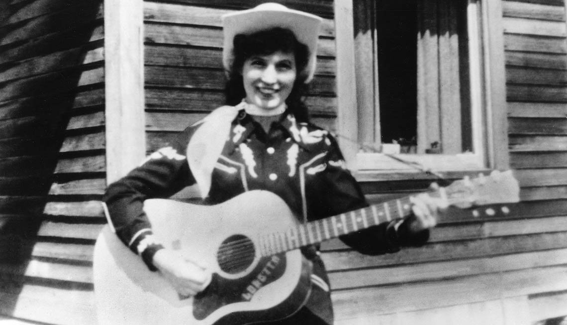 Loretta Lynn holds her acoustic guitar as she poses for a portrait wearing a cowboy hat, a scarf and western shirt outside a log cabin in circa 1960.