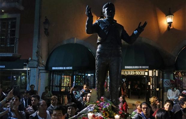 Personas congregadas alredor de la estatua de Juan Gabriel en Guadalajara, México, después de saber de su muerte.