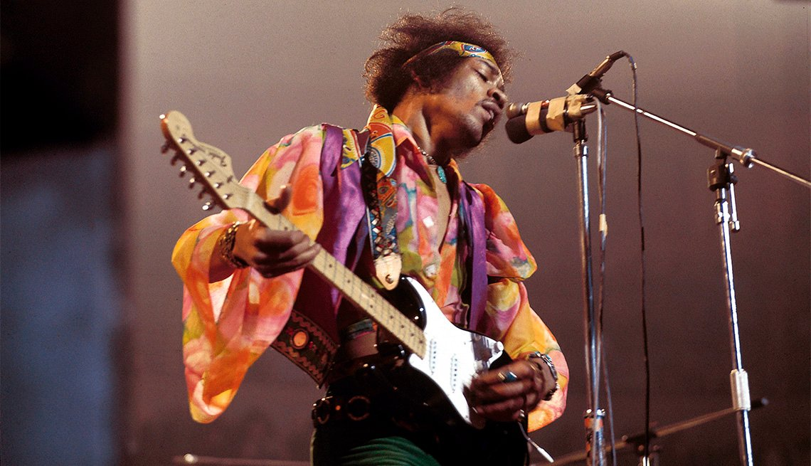 Jimi Hendrix performing live onstage, playing black Fender Stratocaster guitar