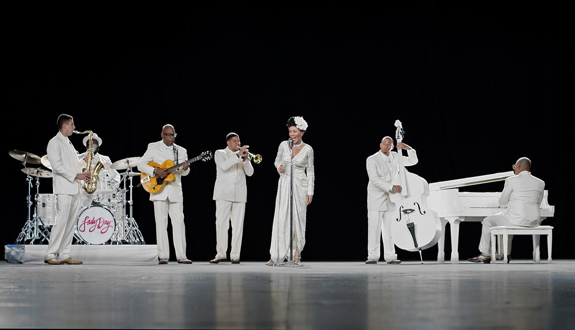 band on stage all dressed in white playing instuments